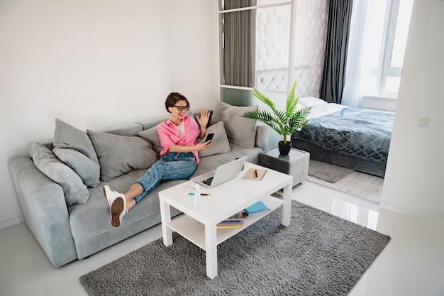 Atrakcyjna uśmiechnięta kobieta w różowej koszuli siedząca zrelaksowana na kanapie w domu w nowoczesnym wnętrzu pokoju przy stole, pracująca online na laptopie w domu