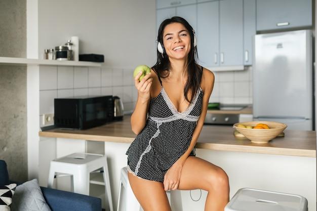 Atrakcyjna uśmiechnięta kobieta w seksownej piżamie jedzącej rano śniadanie w kuchni, zdrowy tryb życia, jedzenie jabłka, słuchanie muzyki na słuchawkach