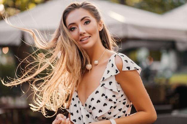 Atrakcyjna uśmiechnięta kobieta z długimi włosami, szczęśliwa zabawa w słoneczny letni dzień
