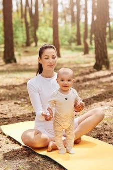 Atrakcyjna uśmiechnięta matka trzymająca niemowlę, gdy dziecko stoi na karemacie w lesie