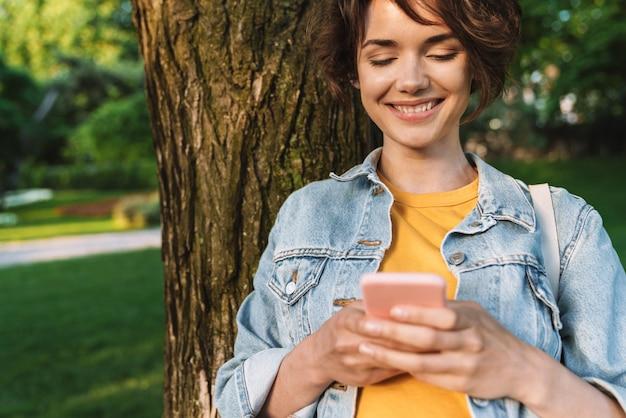 Atrakcyjna uśmiechnięta młoda dziewczyna w swobodnym stroju spędzająca czas na świeżym powietrzu w parku, opierając się na drzewie, korzystająca z telefonu komórkowego