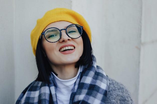 Atrakcyjna uśmiechnięta młoda dziewczyna w szkłach w żakiecie i żółtym berecie na prostym lekkim tle