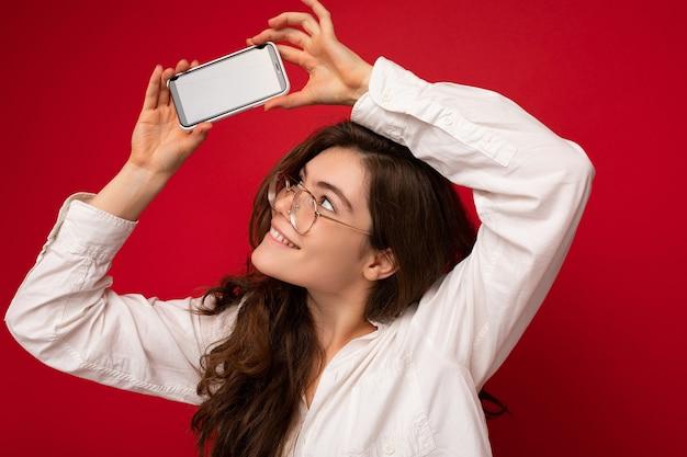 Atrakcyjna uśmiechnięta młoda kobieta brunet ubrana w białą koszulę i okulary optyczne odizolowane na czerwono