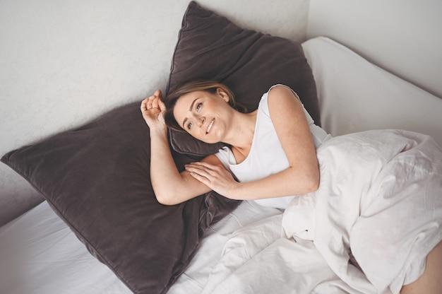 Atrakcyjna uśmiechnięta młoda kobieta rozciągająca się w łóżku budzi się sama szczęśliwa koncepcja, budzi się po zdrowym śnie w wygodnym wygodnym łóżku i materacu dzień dobry