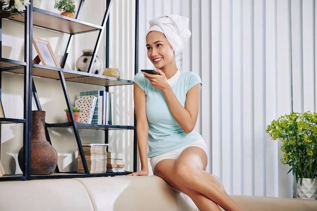 Atrakcyjna uśmiechnięta młoda kobieta siedzi na kanapie i nagrywa wiadomość głosową dla swojego przyjaciela