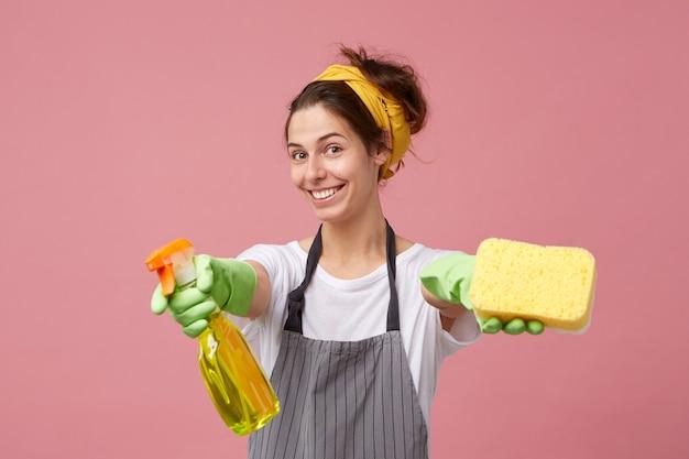 Atrakcyjna, uśmiechnięta młoda kobieta ubrana w zwykły strój i odzież ochronną, rozpościerającą ramiona sprayem do czyszczenia i gąbką, jakby mówiła: czy zechciałabyś mi pomóc w pracach domowych?