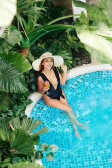 Atrakcyjna uśmiechnięta młoda kobieta w stroju kąpielowym delektująca się słodkim koktajlem z marakui podczas relaksu w basenie