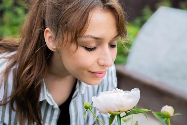 Atrakcyjna uśmiechnięta młoda kobieta wąchania różowej piwonii w ogrodzie wiejskiego domu
