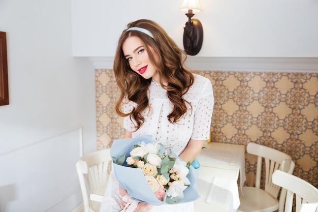Atrakcyjna uśmiechnięta młoda kobieta z długimi kręconymi włosami stojąca i trzymająca bukiet kwiatów w kawiarni