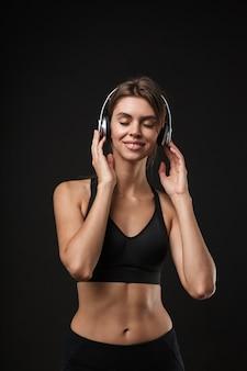 Atrakcyjna uśmiechnięta młoda zdrowa kobieta fitness ubrana w sportowy stanik i szorty na białym tle na czarnym tle, słuchająca muzyki przez słuchawki