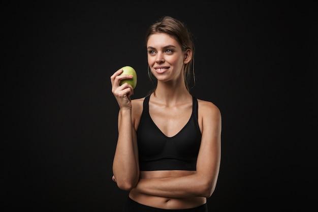 Atrakcyjna uśmiechnięta młoda zdrowa kobieta fitness ubrana w sportowy stanik i szorty na białym tle na czarnym tle, trzymająca zielone jabłko