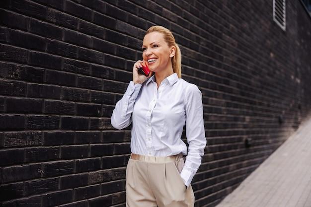 Atrakcyjna uśmiechnięta modna kobieta spaceru na świeżym powietrzu i rozmawia przez telefon.