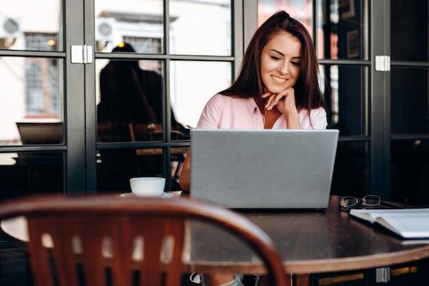 Atrakcyjna, uśmiechnięta niezależna dziewczyna pracuje na komputerze w kawiarni.