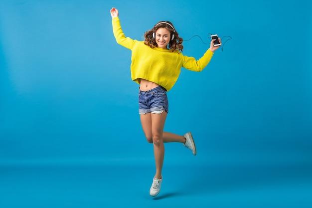 Atrakcyjna uśmiechnięta szczęśliwa kobieta skoki, taniec, słuchanie muzyki w słuchawkach w stroju hipster na białym tle na tle niebieskim studio, na sobie szorty i żółty sweter