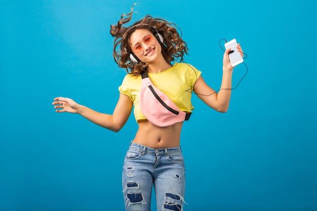 Atrakcyjna Uśmiechnięta Szczęśliwa Kobieta Tańczy Słuchanie Muzyki W Słuchawkach Ubrana W Stylowy Strój Hipster Na Białym Tle Na Tle Niebieskim Studio, Na Sobie Kolorowe Ubrania Darmowe Zdjęcia