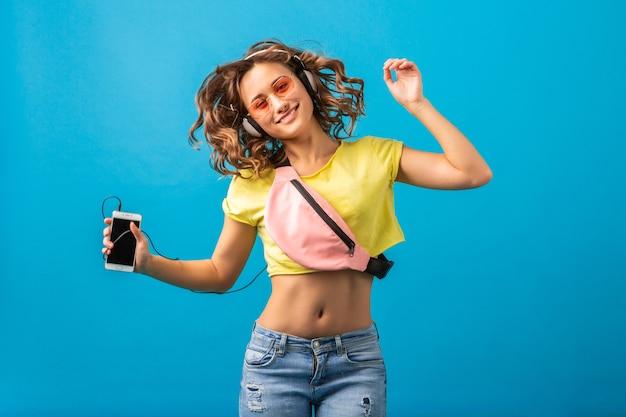 Atrakcyjna uśmiechnięta szczęśliwa kobieta tańczy słuchanie muzyki w słuchawkach ubrana w stylowy strój hipster na białym tle na tle niebieskim studio, na sobie kolorowe ubrania