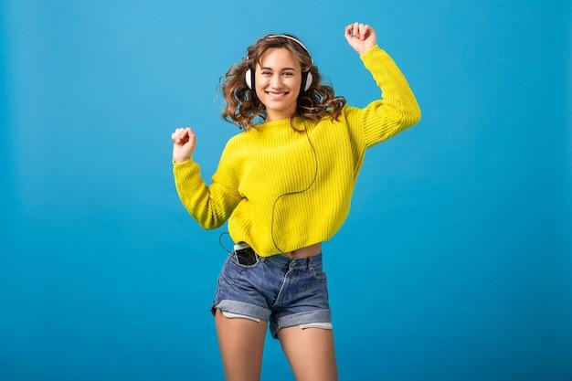 Atrakcyjna uśmiechnięta szczęśliwa kobieta tańczy słuchanie muzyki w słuchawkach w stylowy strój hipster na białym tle na tle niebieskiego studia, na sobie szorty i żółty sweter