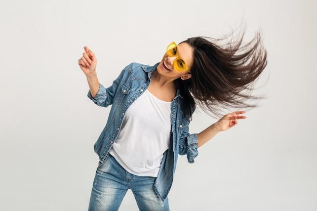 Atrakcyjna uśmiechnięta szczęśliwa kobieta taniec macha długimi włosami na białym tle na białym studio