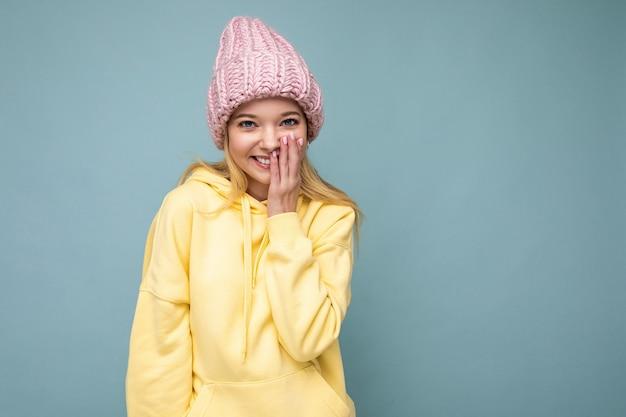 Atrakcyjna uśmiechnięta szczęśliwa młoda blond kobieta stojąca na białym tle nad kolorowym tle ściany noszenie