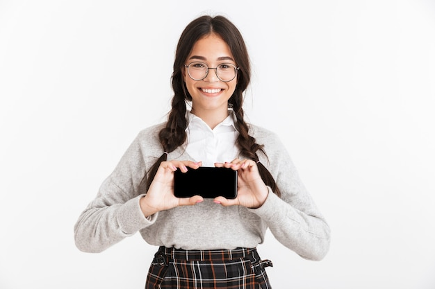Atrakcyjna uśmiechnięta uczennica w mundurze stojącym na białym tle nad białą ścianą, pokazująca pusty ekran telefonu komórkowego