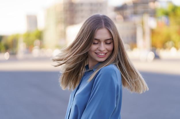 Atrakcyjna wesoła blondynka z latającymi długimi włosami, uśmiechając się, śmiejąc się w mieście
