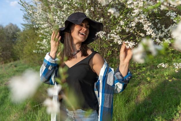 Atrakcyjna wesoła dziewczyna w kapeluszu wśród kwitnących drzew na wiosnę, w stylu casual