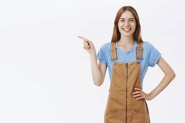 Atrakcyjna wesoła dziewczyna wskazując palcem w lewo w logo, ogłosić ofertę