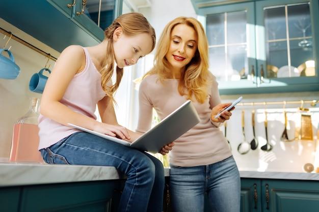 Atrakcyjna wesoła jasnowłosa dziewczyna uśmiecha się i pracuje na laptopie i siedzi na stole, podczas gdy jej matka stoi obok niej z telefonem