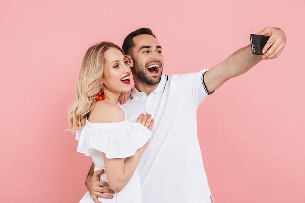 Atrakcyjna wesoła młoda para stojąca razem na białym tle nad różowym, biorąca selfie