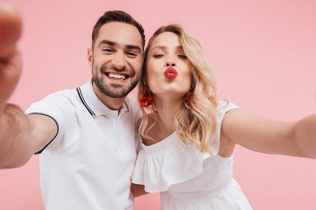 Atrakcyjna wesoła młoda para zakochana stojąca razem na białym tle nad różowym, biorąca selfie