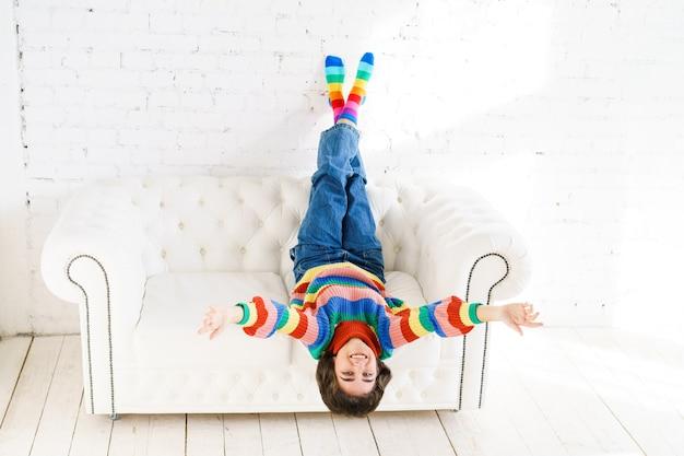Atrakcyjna wesoła pani unosi ręce do góry, aby wyrazić aprobatę, ubrana w krótki pasiasty sweterek, podczas gdy...
