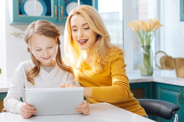 Atrakcyjna, wesoła, szczupła jasnowłosa, szczupła matka, siedząc przy stole, uśmiechając się i używając tabletu z córką