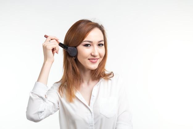 Atrakcyjna wizażystka lub koreańska wizażystka trzymająca pędzle do makijażu na białej ścianie