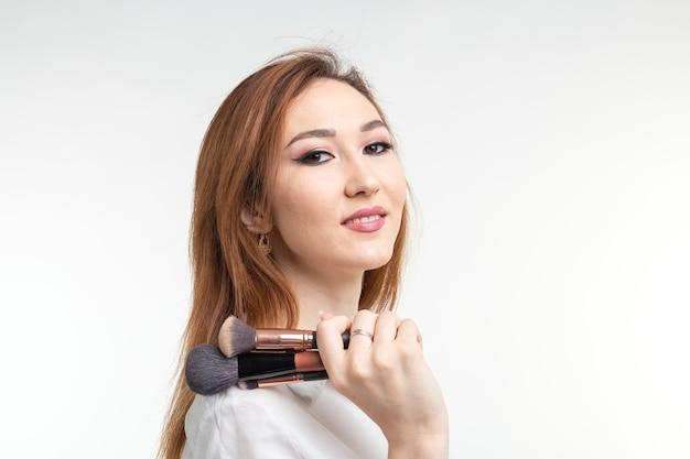 Atrakcyjna wizażystka lub koreański wizażystka trzyma pędzle do makijażu na białym tle