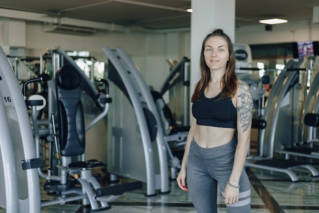 Atrakcyjna wysportowana dziewczyna stoi na ścianie symulatorów na siłowni. zdrowy tryb życia.