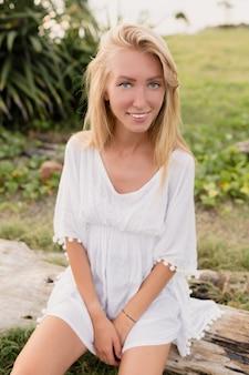 Atrakcyjna wysportowana kobieta o długich blond włosach, dużych niebieskich oczach i czystej skórze ubrana w białą sukienkę siedzącą na drewnie