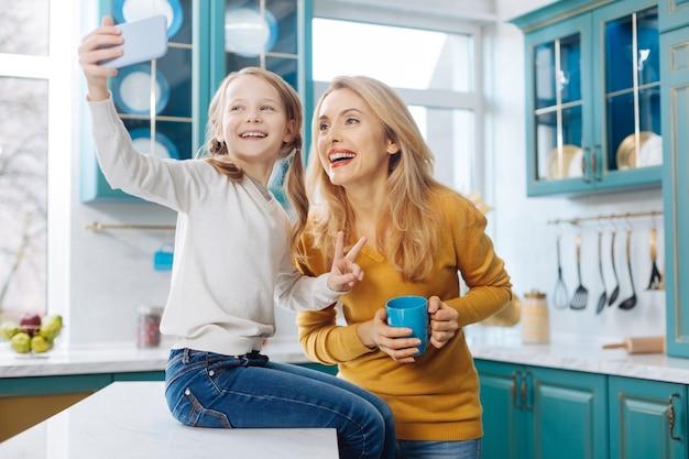 Atrakcyjna, zainspirowana jasnowłosa szczupła matka, uśmiechnięta i trzymająca filiżankę herbaty, podczas gdy jej córka robi zdjęcia