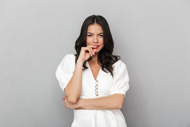 Atrakcyjna zamyślona młoda kobieta w letnim stroju stojąca na białym tle nad szarą ścianą