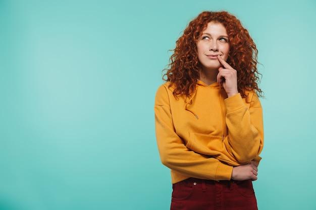 Atrakcyjna zamyślona rudowłosa młoda kobieta stojąca na białym tle