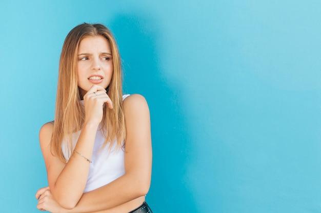 Atrakcyjna zdegustowana młoda kobieta stoi na niebieskim tle