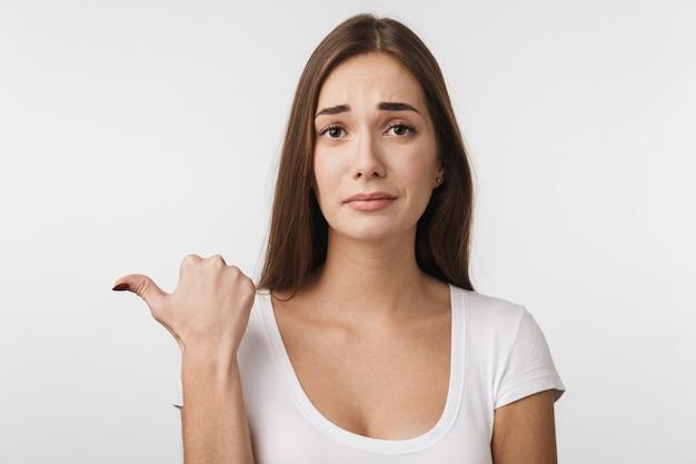 Atrakcyjna zdenerwowana młoda kobieta stojąca na białym tle nad białą ścianą, wskazująca na miejsce na kopię