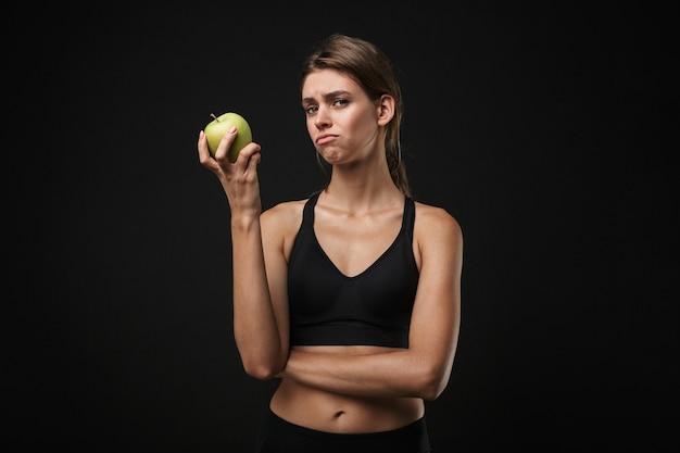 Atrakcyjna zdenerwowana młoda zdrowa kobieta fitness ubrana w sportowy stanik i szorty na białym tle na czarnym tle, trzymająca zielone jabłko