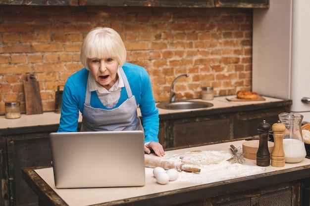 Atrakcyjna zdziwiona zszokowana starsza kobieta gotuje w kuchni. babcia co smaczne pieczenia. za pomocą laptopa.