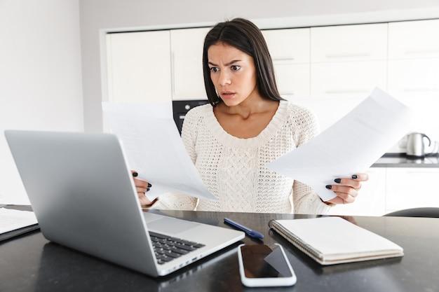 Atrakcyjna, zła, młoda kobieta pracująca z laptopem i dokumentami, siedząc w kuchni, krzycząc