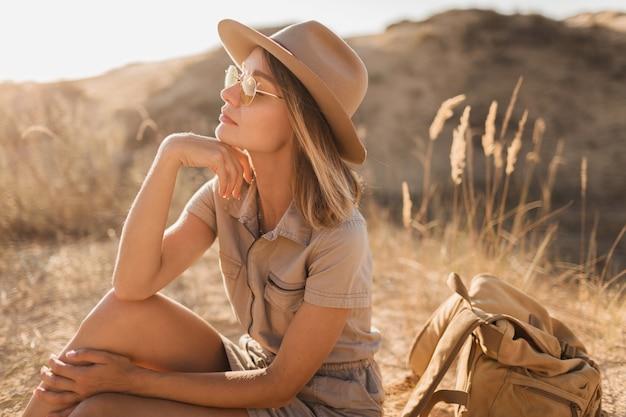 Atrakcyjna, zmysłowa młoda kobieta w sukni khaki spacerująca po pustyni, wędrująca po afryce na safari, ubrana w okulary przeciwsłoneczne, kapelusz i plecak