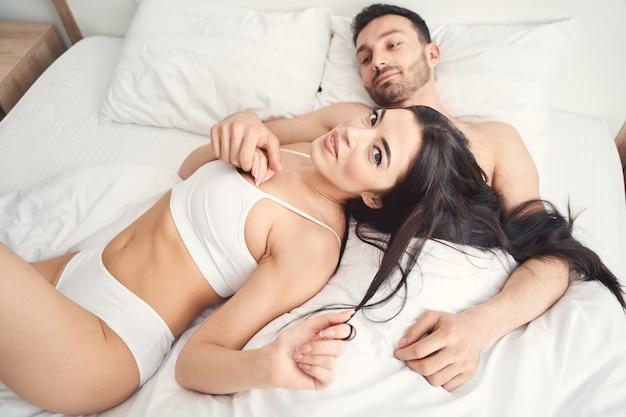 Atrakcyjna zrelaksowana młoda kobieta w bieliźnie leżąca w łóżku obok pogodnego przystojnego męża