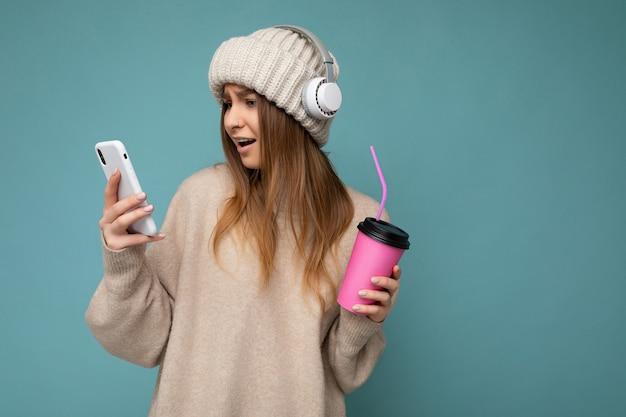 Atrakcyjna zszokowana młoda blondynka ubrana w beżowy sweter i beżowy kapelusz białe słuchawki na białym tle