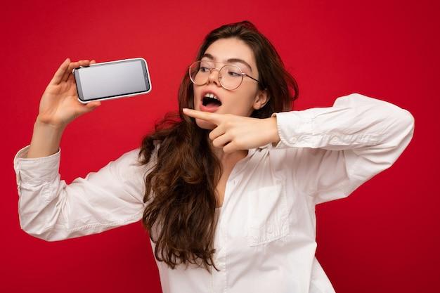 Atrakcyjna zszokowana młoda brunetka ubrana w białą koszulę i okulary optyczne odizolowane na czerwono