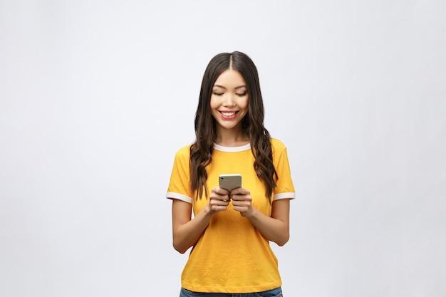 Atrakcyjne azjatyckie nastolatka patrząc na jej ekran telefonu komórkowego z radosną miną