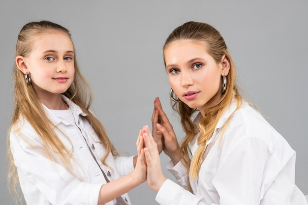 Atrakcyjne długowłose panie o niebieskich oczach i białych strojach trzymające się za ręce